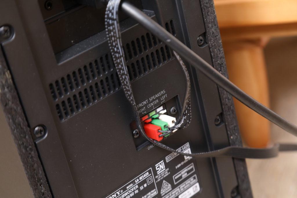 由於 Soundbar 本體要微細化,輸入和前置擴音機部分,其實是在低音揚聲器中,和 Soundbar 之間也是以有線方式操作,因此擺放時需照顧包括 HDMI在內的多條線,只有放在電視櫃旁。